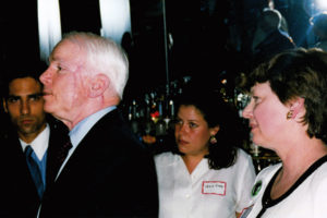 Senator John McCain speaks at a REP reception in his honor in June 2000. REP President Martha Marks is at his side. His face shows the scars of a recent cancer surgery.