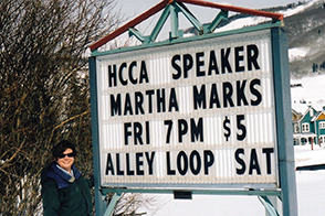 Martha poses with a sign announcing her upcoming speech to the High Country Conservation Advocates in Crested Butte, CO.